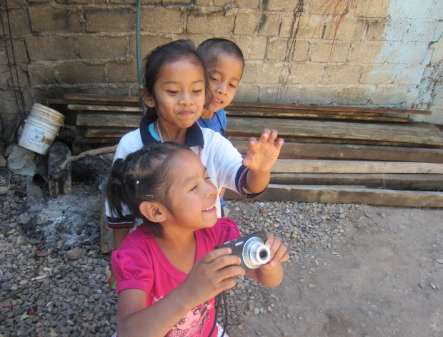 Children in Cuernavaca play with a camera. Photo by Kirsten Fenn