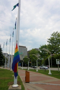 The rainbow colours hangs below the permanent flags at City Hall before the ceremony. Photo by Kirsten Fenn